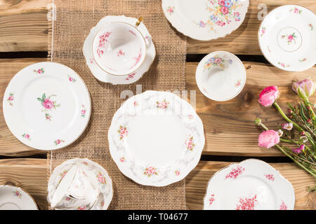 Old romantic porcelain, pink flowers arranged on rustic wood planks. Shot from above, flat lay. - Stock Photo