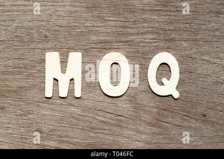 Alphabet letter in word MOQ (Abbreviation of Minimum Order Quantity) on wood background - Stock Photo