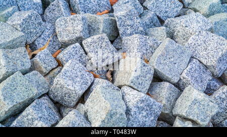 Heap of white small bricks covered in small white stones these bricks is one of the many varieties being displayed - Stock Photo