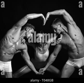 Circus gymnasts at pilates or yoga training. Twins men with muscular body and girl. Gymnastic school and energy. Fitness and dieting. valentines day - Stock Photo