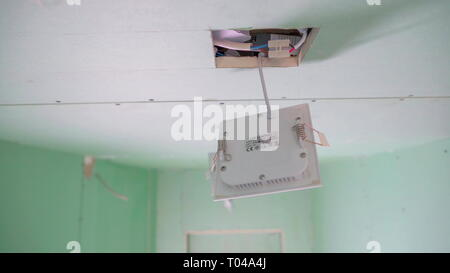 The white wires inside the ceiling with the white box hanging on the square hole of the ceiling of the house - Stock Photo