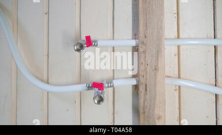 The white pipes used for water sources in the house attached on the wooden wall of the house - Stock Photo