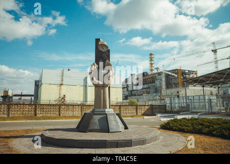 Monument to the Chernobyl Liquidators and fourth reactor without enclosing sarcophagus. Chornobyl Nuclear Power Plant - ChNPP. Radioactive zone in - Stock Photo