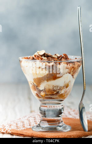 Trifle. Homemade Layered dessert made of biscuit and cream cheese (mascarpone or yogurt) with chocolate and nuts in a glass. Tiramisu. Cheesecake. Sel - Stock Photo