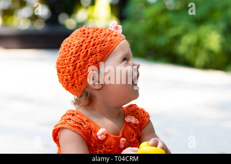 a girl in an orange knitted dress and hat is surprised, rejoices, screams, cries, raises her hands. children's fashion concept. - Stock Photo