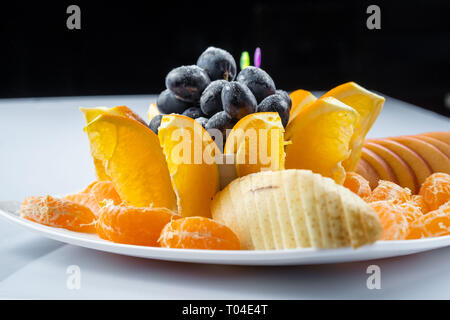 Mixed fruit in white plate isolated on white background - Healthy food style - Stock Photo