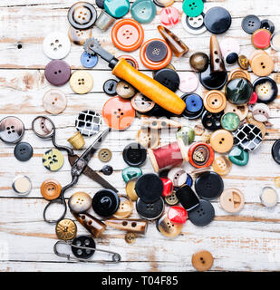 Spools of threads and buttons on wooden table.Scissor, sewing buttons and thread