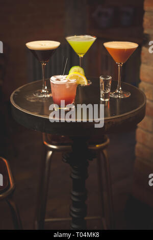 colourful collection of martinis on bar table - Stock Photo