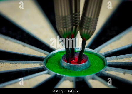 macroshot of three darts in the bulls eye of a dartboard - Stock Photo