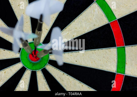three darts thrown at the bulls eye of a dartboard - Stock Photo