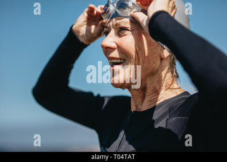 Portrait of a smiling senior woman in swimming costume standing outdoors. Senior woman taking off her swimming goggles after a swim.