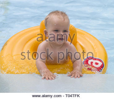 unny baby boy on summer vacation. Kid having fun in swimming pool - Stock Photo