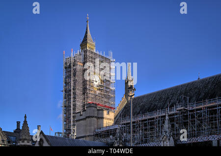The iconic London landmark Elizabeth Clock Tower, Big Ben, with one dial showing and covered in steel scaffolding for renovations and repair. - Stock Photo