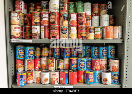 Storage shelves in a Trussell Trust local church food bank warehouse in the UK showing tins of baked beans and soup ready for food parcels - Stock Photo