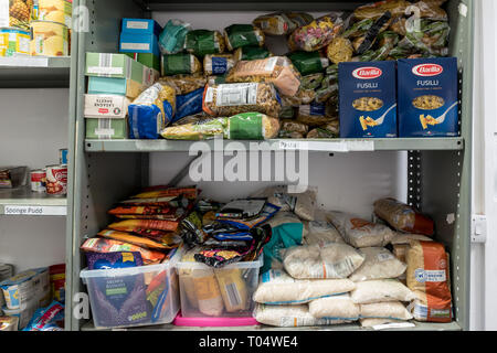 Storage shelves in a UK Trussell Trust local church food bank warehouse showing packets of dry goods, rice and pasta, ready for food parcels - Stock Photo