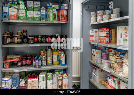 Storage shelves in a UK Trussell Trust local church food bank warehouse showing milk, juice, jams and porridge ready for food parcels - Stock Photo