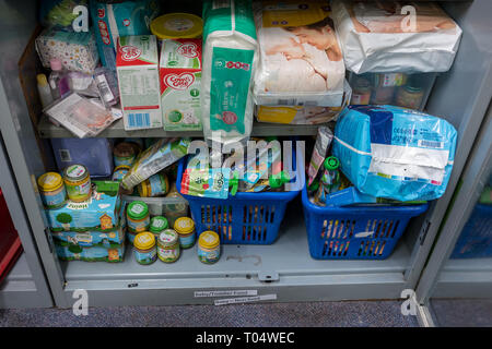 Storage shelves in a UK Trussell Trust local church food bank warehouse showing baby food, toiletries, milk and nappies ready for food parcels - Stock Photo