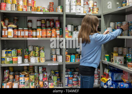 A young female volunteer working at a local church UK food bank (Trussell Trust) organises tins and donations ready for parcels for clients in need - Stock Photo