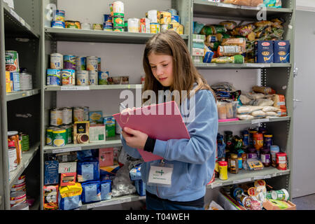 A young female volunteer working at a UK Trussell Trust local church food bank stands in a foodbank warehouse with a clipboard & parcel packing sheet - Stock Photo