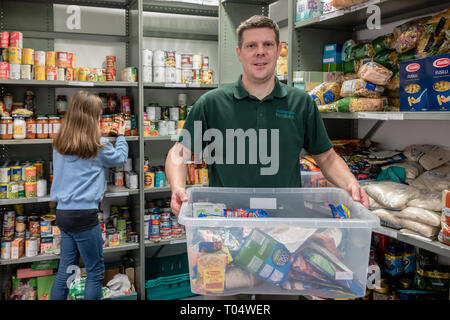 Volunteer workers in a UK Trussell Trust local church food bank packing shelves and holding donations - Stock Photo