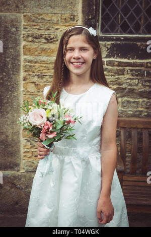 Beautiful smiling tween or teen young bridesmaid holding a rustic wildflower bouquet, wearing a white dress, in front of a vintage stone church - Stock Photo