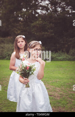 Sweet child and young teen girl bridesmaids wearing short white dresses, holding hand-tied bouquets with foliage in a park waiting - Stock Photo