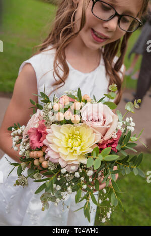 Girl bridesmaid holding small rustic seasonal September hand-tied wedding bouquet: pastel pink roses, dahlia, gypsophilia, astrantia, berries, foliage - Stock Photo