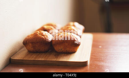 Six delicious home-made muffins on a wooden background. Dessert for gourmet. Selective focus - Stock Photo