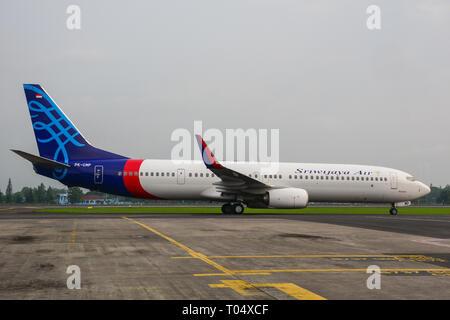 Yogyakarta, Indonesia - Apr 15, 2016. A Boeing 737-900ER airplane of Sriwijaya Air docking at Adisucipto International Airport (JOG). - Stock Photo