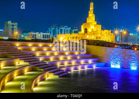 Stairs of small amphitheater at Souq Waqif Garden near Doha Corniche with Doha mosque at night. Doha city center in Qatar, Middle East, Arabian - Stock Photo