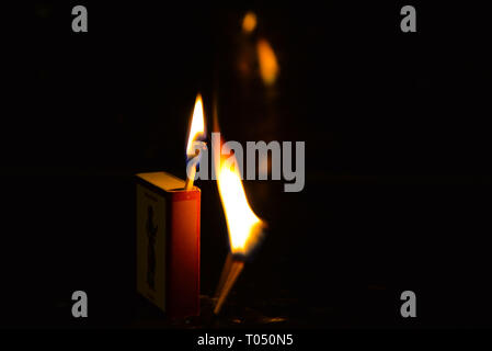 Box of matches with two matches lit against a dark background. - Stock Photo