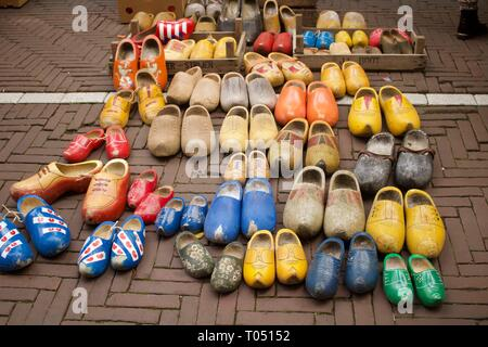 Selection of second hand clogs displayed for sale on ground - Stock Photo