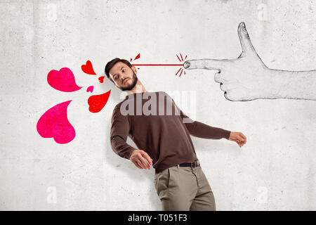 Young handsome man in casual clothes standing in half-turn near wall and leaning back as if from hand-drawn finger gun shooting pink hearts at him. - Stock Photo