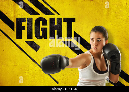 Crop close-up of young woman in boxing gloves holding one hand out, against yellow wall with 'FIGHT' title and black diagonal lines. - Stock Photo
