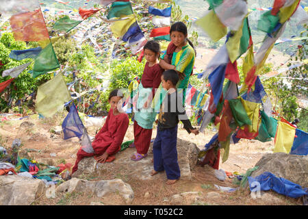 Nepalese family on a hill coverad by traditional prayer flags, Nagarkot, Nepal. - Stock Photo