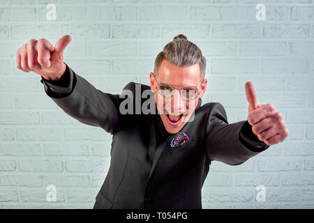 Positive businessman smiling looking at camera showing hand gesture thumbs up sign symbol - Stock Photo