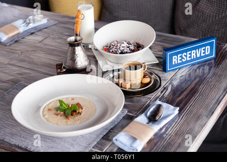 Closeup breakfast with porridge and Turkish coffee in cezve on wooden stand, porcelain cup with sugar cubes served on table in restaurant, reserved pl - Stock Photo