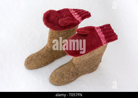Hand-made valenki and mittens on white snow. Traditional Russian clothes and shoes in the winter. - Stock Photo