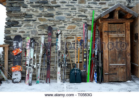 A snowboard and sets of skis, outside a restaurant at the ski resort in Sainte-Foy-Tarentaise, Auvergne-Rhône-Alpes region in south-eastern France. - Stock Photo