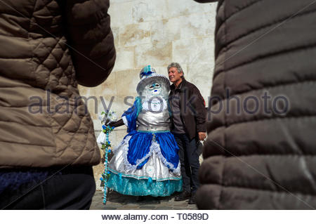 A man poses for photos next to a participant at the Annecy Venetian Carnival. Annecy. Auvergne-Rhone-Alpes, south east France. - Stock Photo