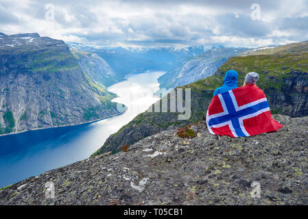Couple sits on rock and looks at mountains near Trolltunga. Popular tourist attraction. Ringedalsvatnet - lake in the municipality of Odda in Hordalan - Stock Photo