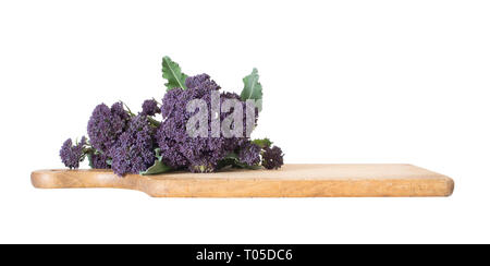 Early purple sprouting broccoli spring vegetable, with wooden food cutting board. Isolated on white. Low angle view. - Stock Photo