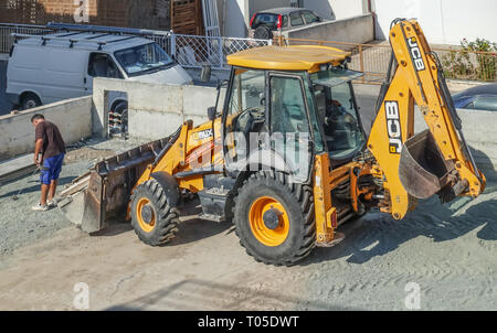 Limassol, Cyprus - November 4, 2018: Large yellow JCB tractor on a building site. Vehicle is large in the frame.  Man with tape measure in front of th - Stock Photo