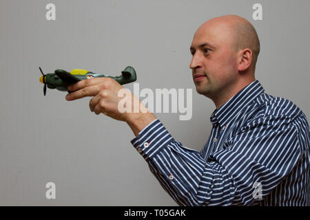 man holding a green airplane and dreaming aboyt flying on a gray background - Stock Photo