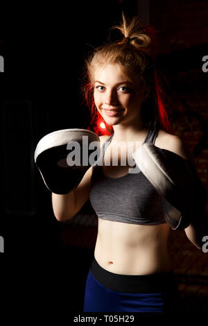 Portrait of smiling woman in boxing gloves. - Stock Photo