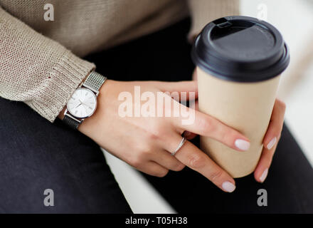 Woman holding glass of coffee in hands. - Stock Photo