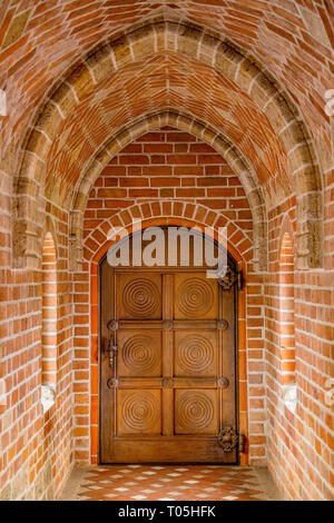 Wooden door in a brick tunnel, close up - Stock Photo