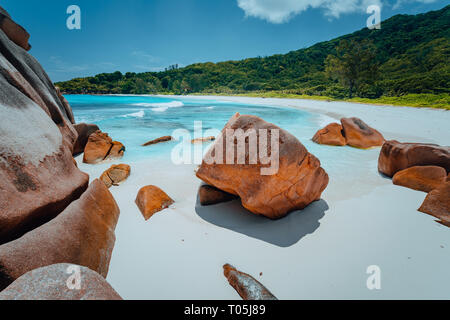 Tropical lagoon with granite boulders in the turquoise water and a pristine white sand at Anse Cocos, La Digue island, Seychelles - Stock Photo