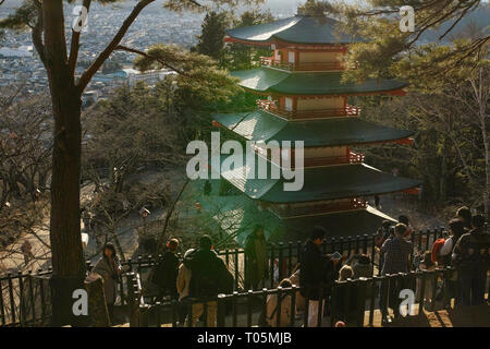 Yamanashi, Japan - 01/05/2019: Tourists grouped together taking pictures while admiring the view from behind chureito pagoda - Stock Photo