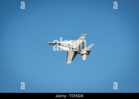 McDonnell Douglas F/A-18 Hornet in flight with contrail around the fuselage - Stock Photo